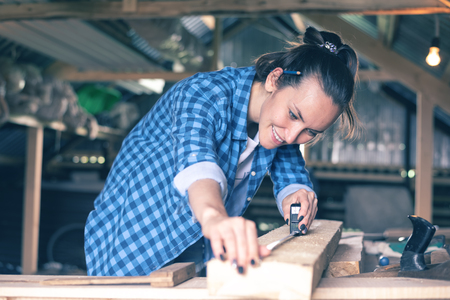 smiling woman in a home workshop measuring tape measure wooden Board before sawing, carpentry