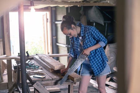 woman engaged in processing wood in home workshop, carpentry Archivio Fotografico