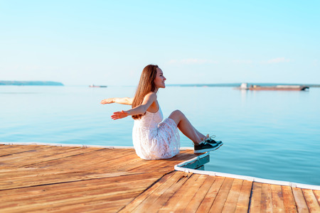 Young girl in white dress sitting on wooden pier with open hands looking into distance of sea, freedom, clean air, dreams Stock Photo