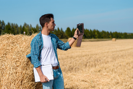 young agronomist in white t-shirt and blue shirt with tablet and notebook stands at haystack, taking pictures of the field