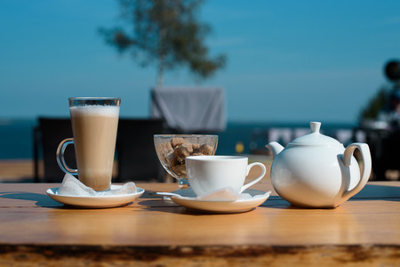 Concept of awakening. set of latte mugs, cup of tea and a teapot with cane sugar on the summer terrace of the cafe 写真素材