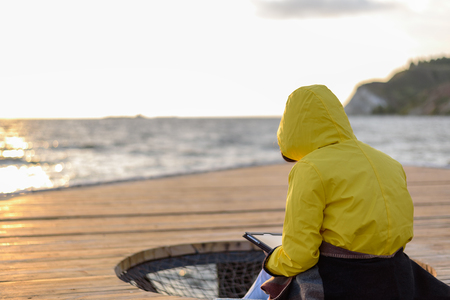 Woman in yellow raincoat from the back sitting on pier with tablet at sunrise