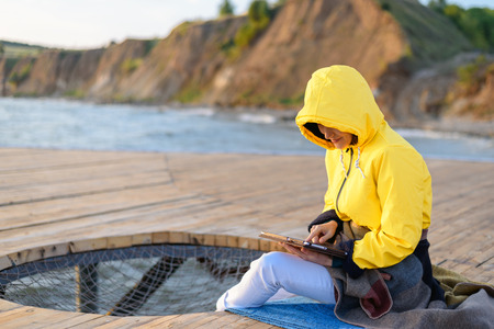 girl in yellow jacket uses tablet sitting on wooden pier by the sea 写真素材