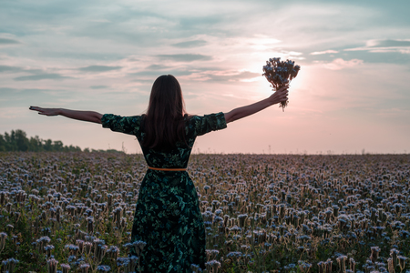 Freedom. Woman with open arms and a bouquet of flowers at sunset on flower meadow