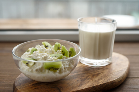 Close - up of cottage cheese with kiwi and glass of milk on wooden Board by window, concept healthy food