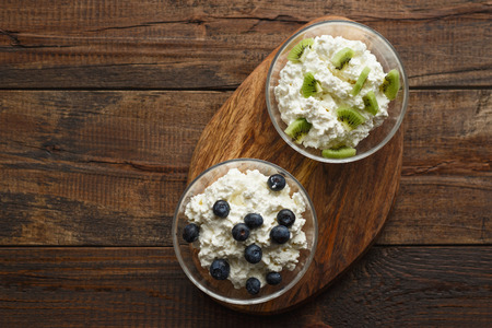 Top view cottage cheese blueberries and kiwis on a wooden stand with natural light with copy space
