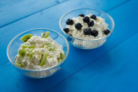 milk product, cottage cheese with berries and fruit in bowls on blue background. Healthy diet Breakfast 写真素材