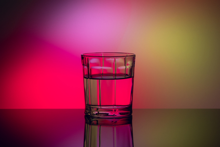 closeup abstract glass with liquid on multicolor background
