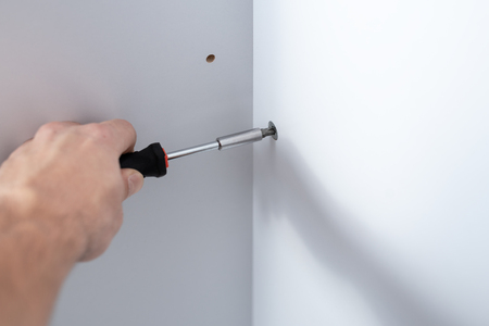 Close-up of a man's hand with a manual screwdriver twists the bolt into a piece of furniture with a copy of the space 스톡 콘텐츠