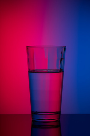 vertical image glass of water on blue pink background. duotone concept