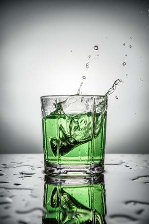abstract image of splash of green water in glass and drops on table on grey background Banque d'images