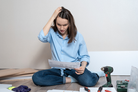 puzzled woman in blue shirt with instructions sits on the floor. concept of furniture assembly