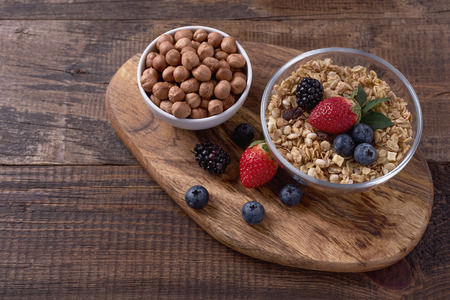 Granola with hazelnuts and berries in bowls on wooden background. Healthy Breakfast concept. Standard-Bild