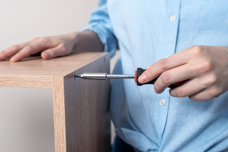 close-up of furniture Assembly with screwdriver in the hands of woman in blue shirt