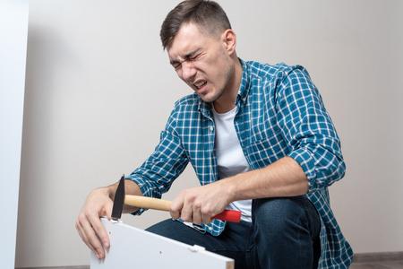 l'uomo in abiti casual ha colpito il pollice con un martello durante l'assemblaggio di mobili, difficoltà, emozione di dolore.