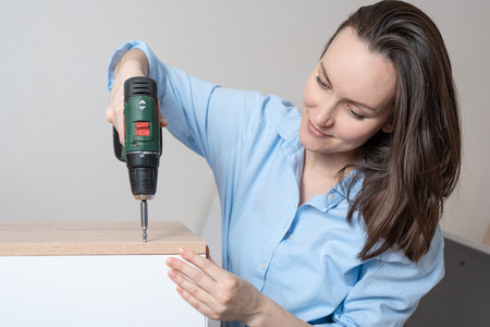 Happy woman in the blue shirt assembling furniture with screwdriver, close up
