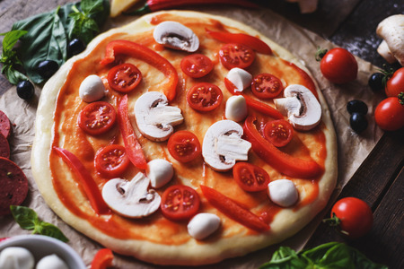 close up uncooked italian homemade pizza with ingredients. process of cooking pizza concept 스톡 콘텐츠