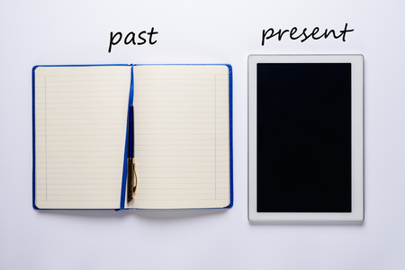 The concept of past and present. Open paper Notepad with pen and modern tablet computer. top view, flat lay Stockfoto