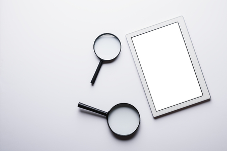 Top view of the tablet, two magnifiers on a white background with space for text. Web search concept, Internet, mock up, flat lay, minimalism, copy space
