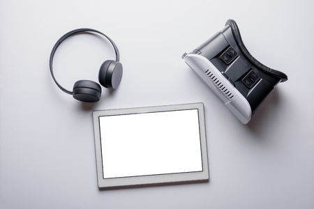 A set of modern devices. Virtual reality glasses, wireless headphones, tablet on a white background, mock up. The concept of high-tech gadgets Standard-Bild
