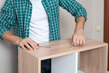 Close-up of a man in a white t-shirt and a plaid shirt twists the bolt with Z-shaped key, collects furniture