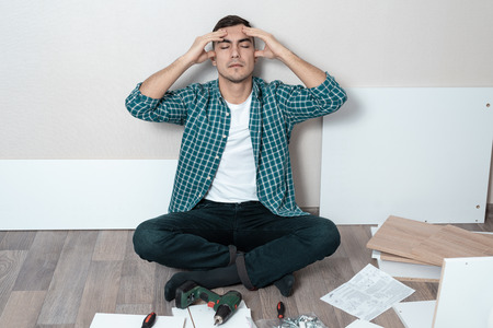Portrait of a man on the floor holding his head, the difficulty of assembling furniture. Stock Photo