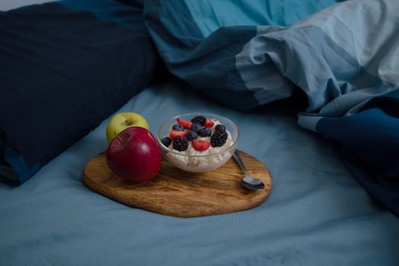 Wooden tray on the bed with bowl of oatmeal and apples. Stockfoto