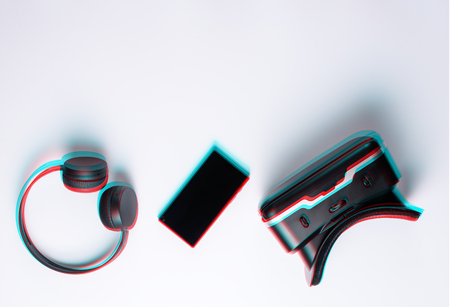 Flat lay modern gamer gadgets,  headphones, smartphone, VR glasses, anaglyph and glitch effect.