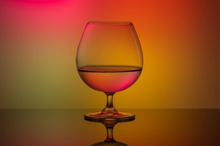 One glass on the table on a multi-colored background.