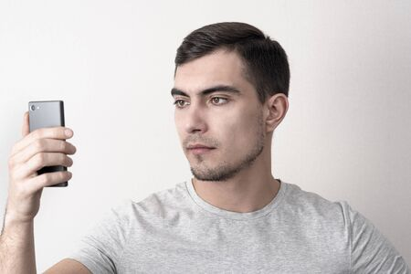Caucasian man in gray t-shirt and smartphone in hand uses face recognition