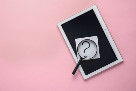 concept of searching internet. tablet, question mark and magnifying glass on a pink background with copy space