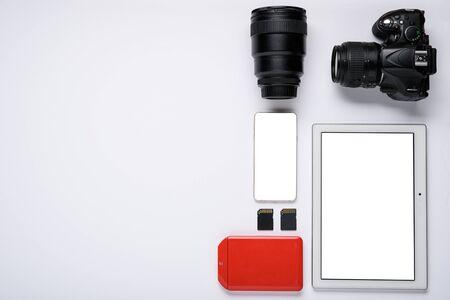 modern set of gadgets. tablet, smartphone, hard drive, SD memory card, DSLR camera, lens. screens for layout