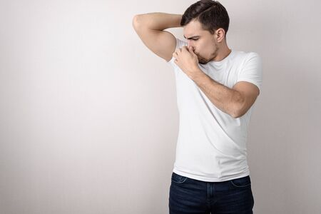 young man in white t-shirt clamps his nose from smell of sweat from his armpits on gray background with copy space