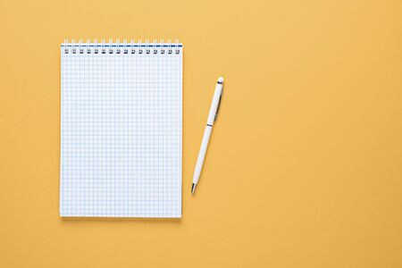 flat lay business composition. Notepad with clean sheet and white pen on yellow background with copy space