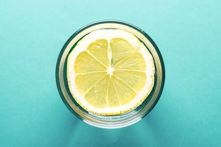 summer detox cocktail. water with lemon top view close-up on turquoise background