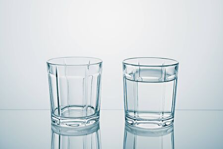 Two glasses one empty, one full of clean water. Banco de Imagens