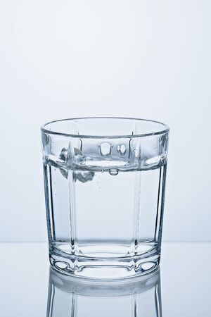 Vertical image glass is full with crystal clear water. Banco de Imagens - 128654050