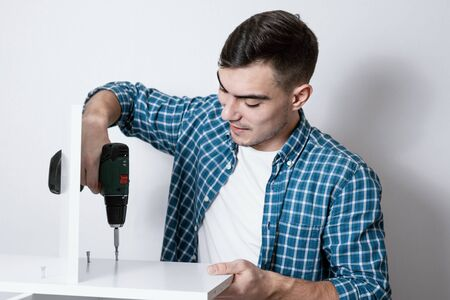 An attractive European man collects furniture with the help of an electric screwdriver