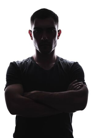 vertical Silhouette portrait of young man folded his hands on his chest, serious expression, stern look