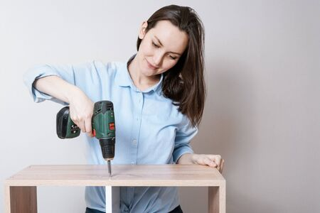 Confident smiling European woman collects wooden furniture with electric screwdriver in hand Stock Photo