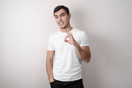 Young European man in white t-shirt on grey background shows OK sign, studio shots Stock Photo