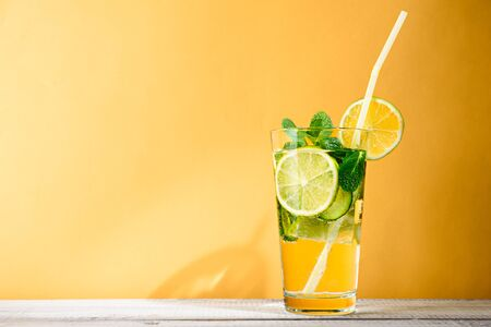 refreshing summer cocktail with lemon, cucumber and mint on yellow background