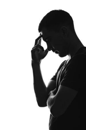 vertical Silhouette portrait profile of thinking young man holding his hand to his forehead, pose of thinker Stock Photo