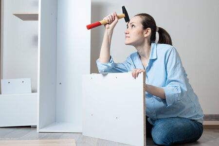 Portrait of thoughtful young white woman with hammer in her hand sitting on the floor and collects white wooden furniture Stock Photo