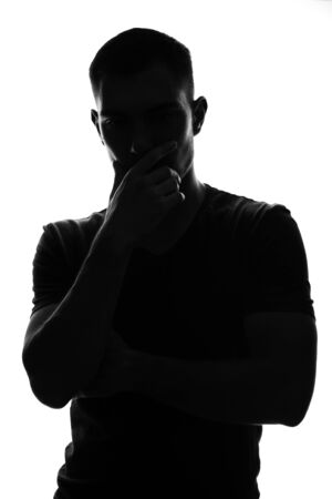 vertical Silhouette portrait of a thoughtful young man holding his hand to his face, pose of thinker
