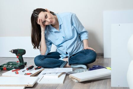 Tired young woman sitting on the floor in front of furniture items, can not collect furniture