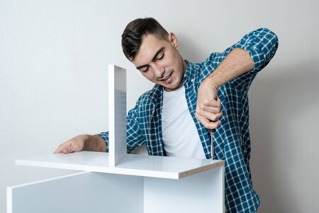 Happy Caucasian man collects white wooden table with hand screwdriver