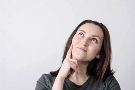 Large portrait of a young European woman on a gray background, hand touches cheek, dreamy look. copy space Stock Photo