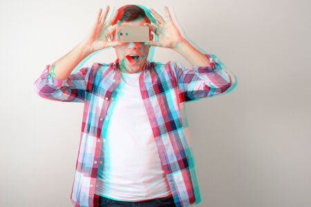 young man in plaid shirt taking pictures with phone on hands, glitch effect Stock Photo