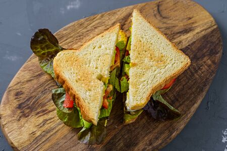 Top view of two juicy sandwiches with toasted bread on wooden Board Stockfoto - 129201382